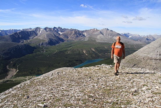 A man hikes along a rocky terrain, a rocky mountain range at his back.