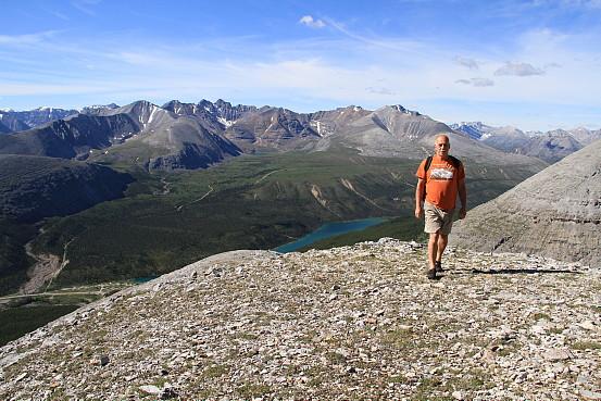 A man hikes along a rocky terrain, a rocky mountain range at his back.
