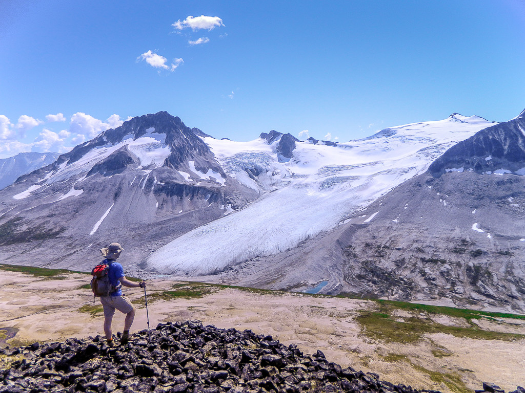 A hiker pauses on a rocky terrain to take in the view of an ancient glacier.