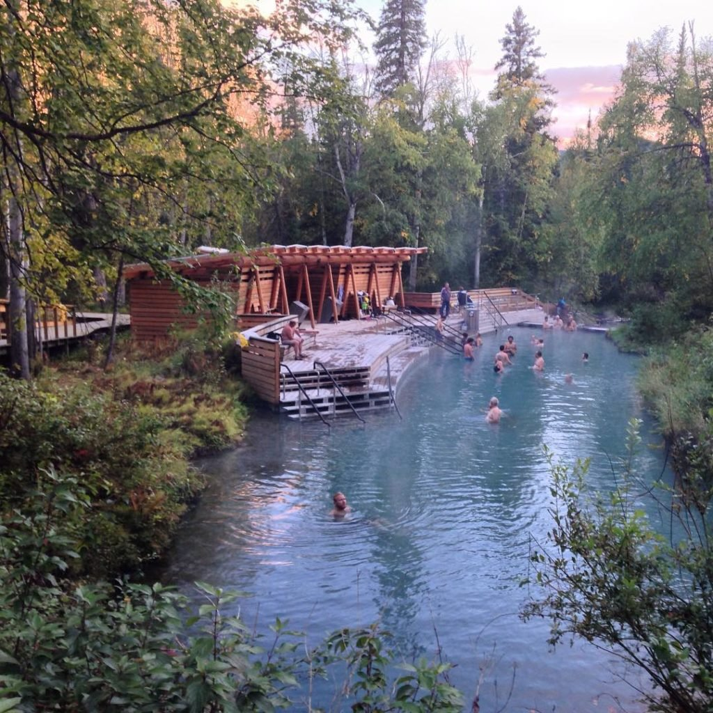 Groups of people enjoy a dip in Lizard Hot Springs.