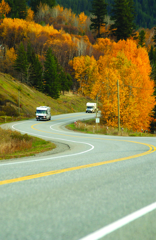 Two RVs travel along Highway 97, lined with brightly coloured fall trees.