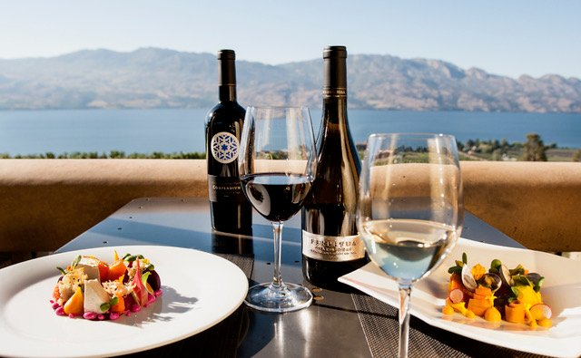 A table with a mountain view is set with two colourfully plated dishes, two bottles of wine, one glass of red wine, and one glass of white.