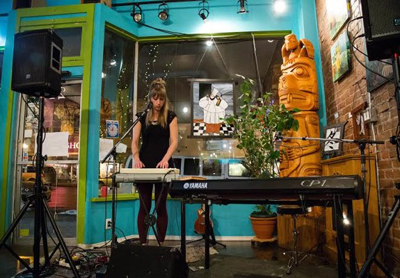 A woman plays keyboard in an eclectic cafe.