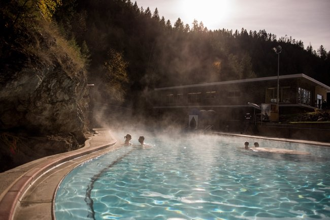 People relax in a crystal-clear hot spring pool, surrounded by trees.