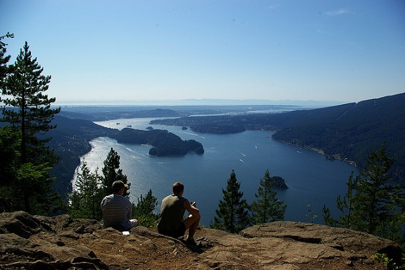Two hikers sit at the edge of a lookout taking the water views.