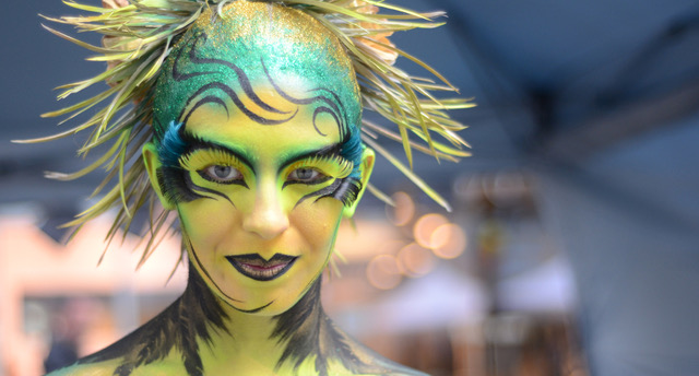 A woman is intricately painted as a yellow, green, and blue bird-like creature.