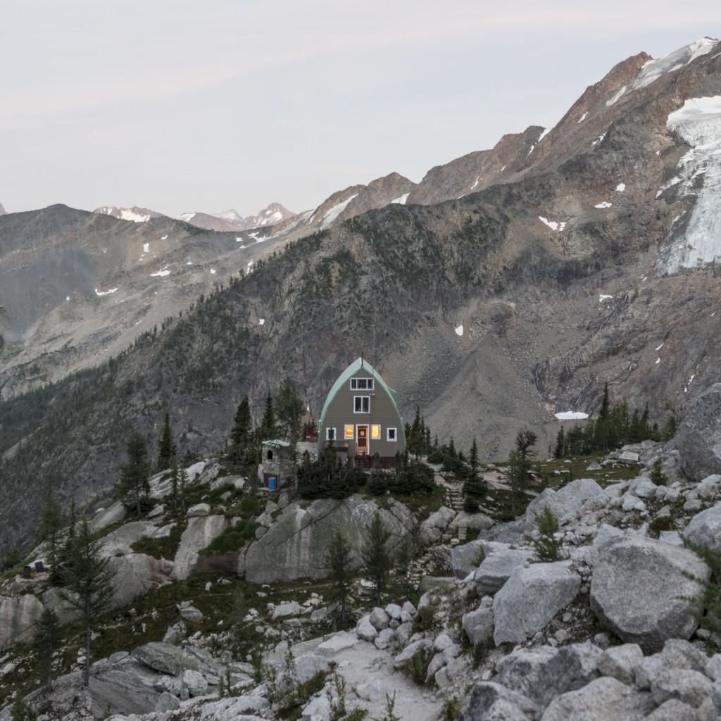 An a-frame cabin nestled in a rocky landscape.