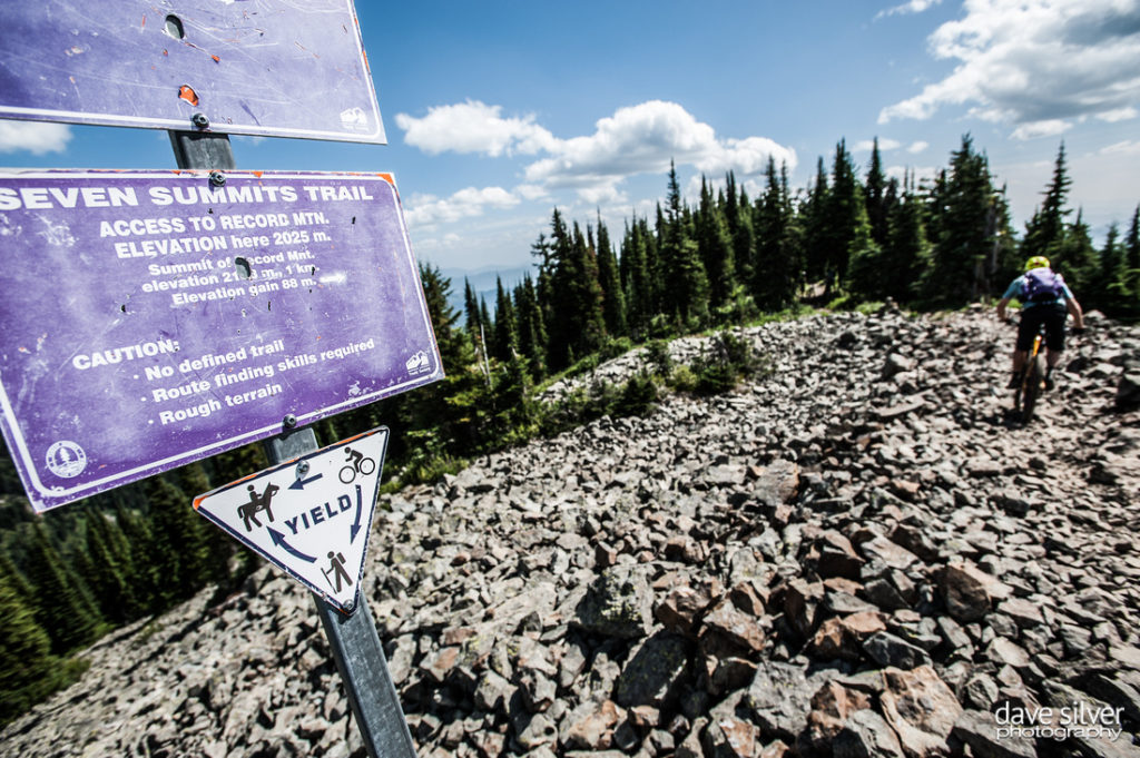 "A man pedals on a rocky terrain and a sign that reads ""Seven Summits Trail""."