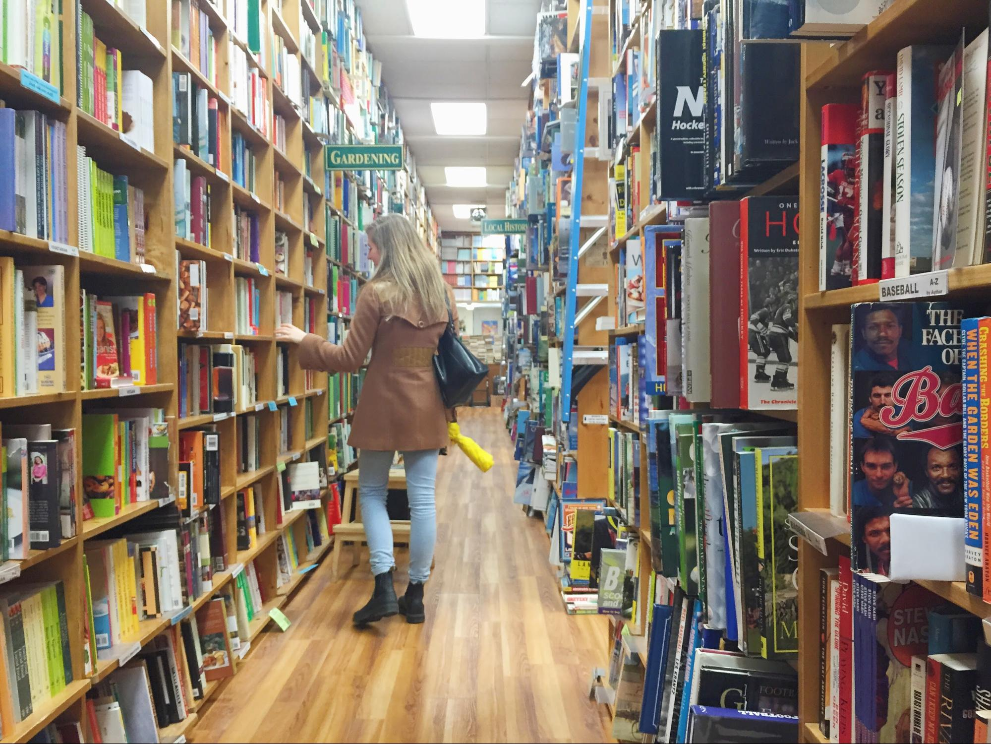 A woman explores the aisles of a used bookstore.