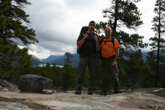 Two men pause for a picture while hiking in a rocky terrain.