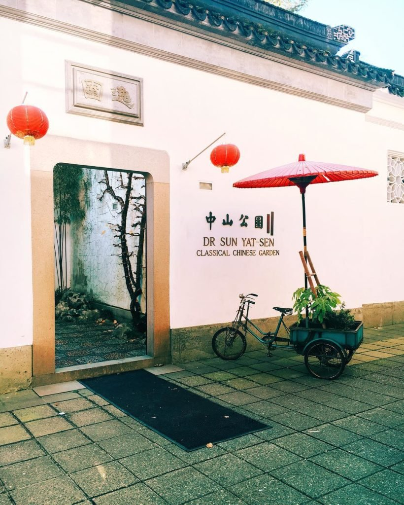 A bike with a wagon attached sits outside the stone exterior of the Yat-Sen Classical Chinese Garden.