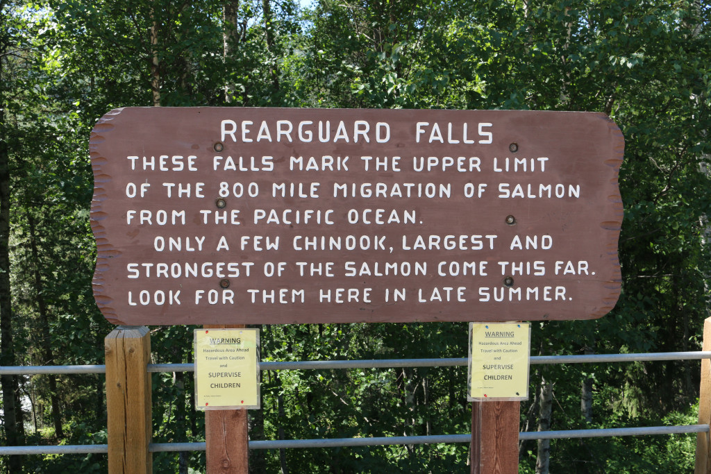 "A large brown wooden sign that reads ""Rearguard Falls"" and describes the local salmon migration."