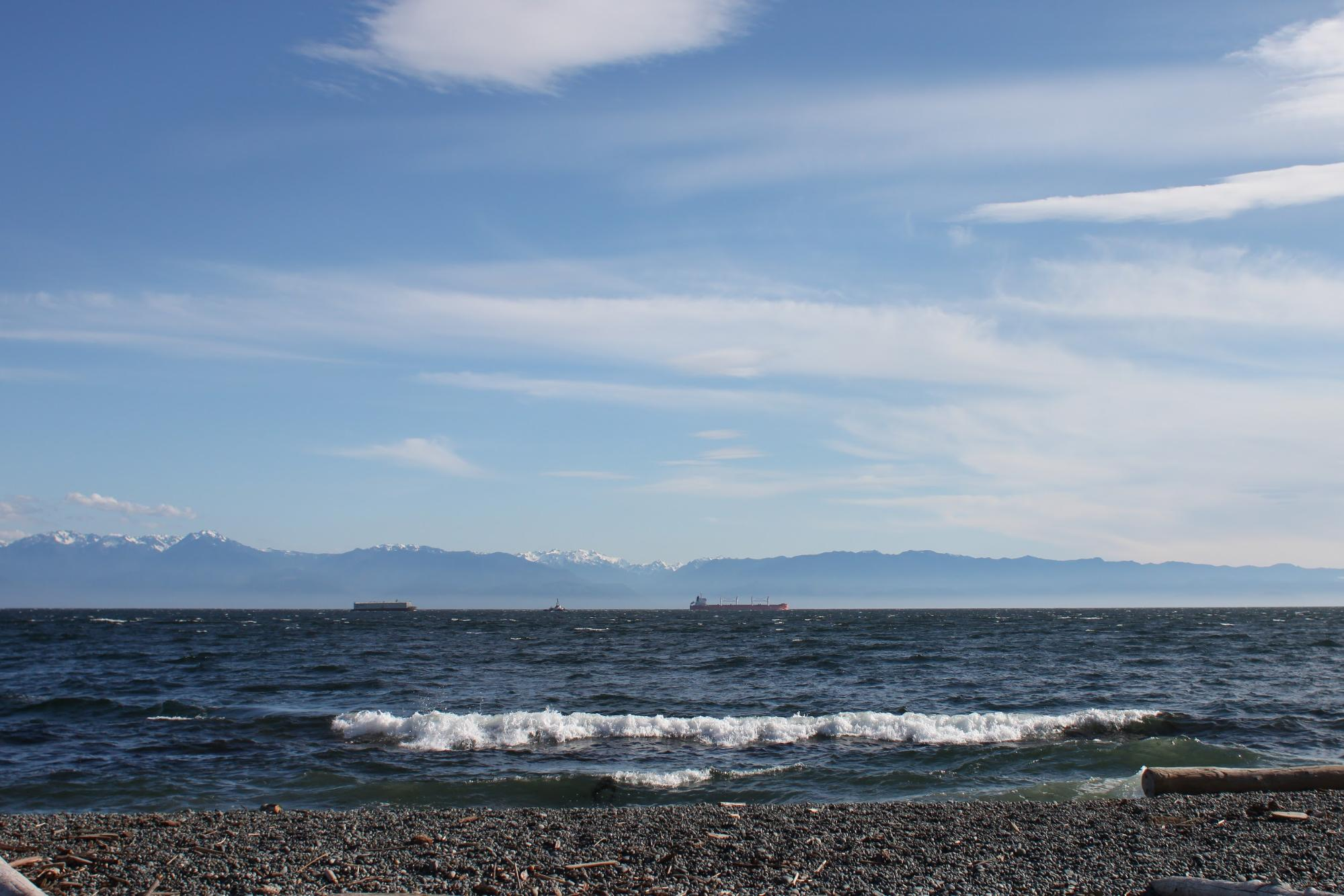Waves lap a rocky beach under a blue sky.