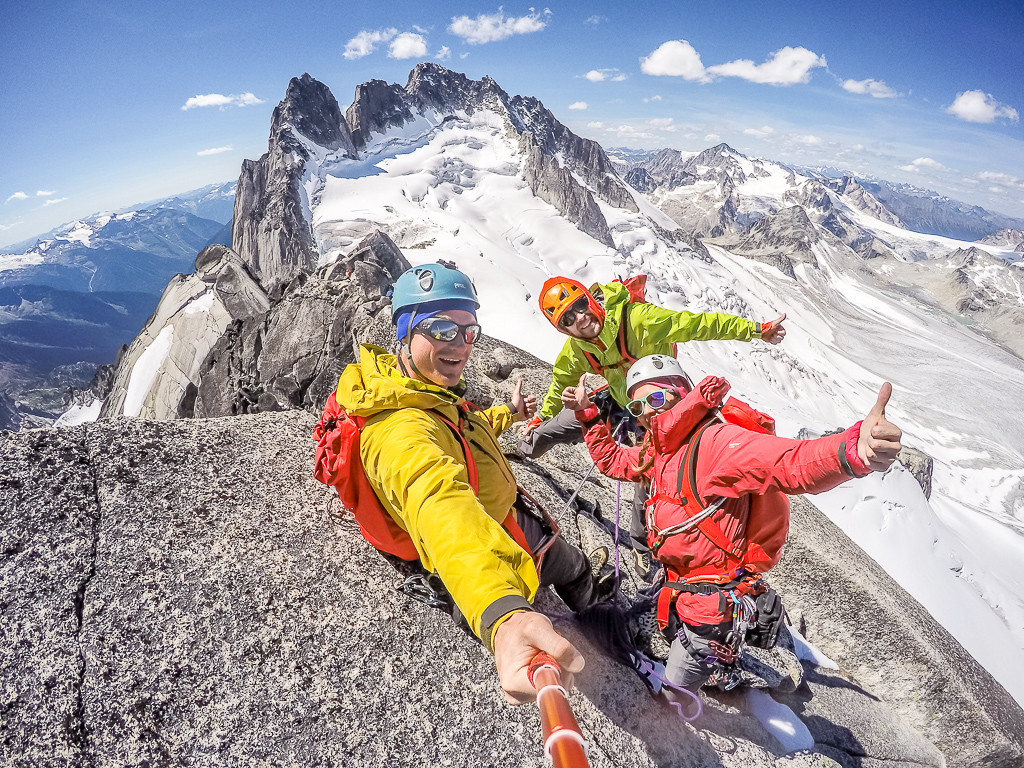 Three hikers celebrate with a selfie on the peak of a mountain.
