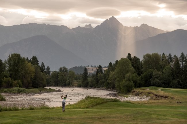 A golfer tees off on a lush golf course with mountain views.