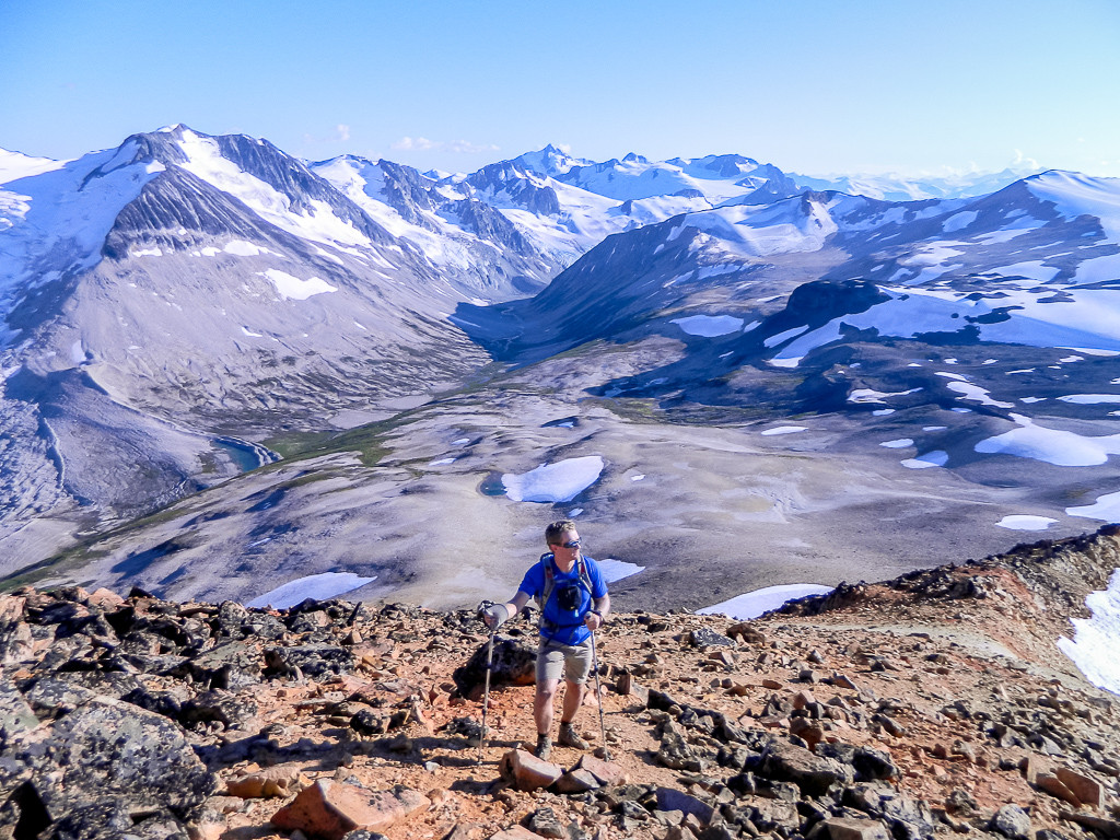 Hiking up a rocky terrain with sweeping, snow-covered mountain vistas behind you.