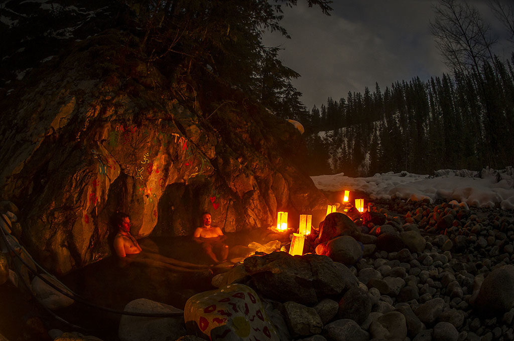 People enjoy an evening hot springs soak, lit by lanterns.