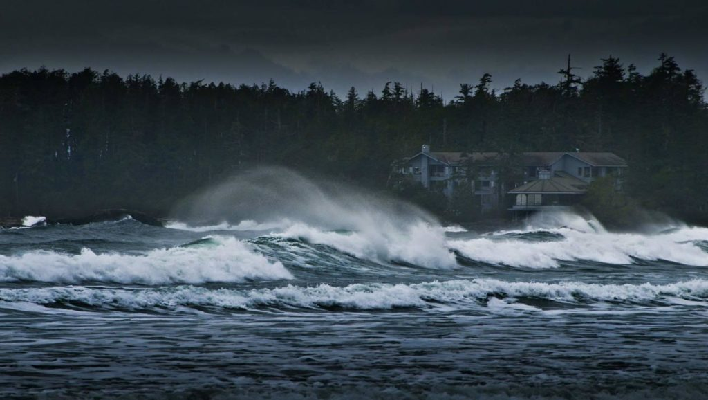 Angry waves crash the shore under a dark sky.