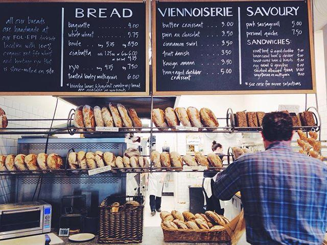 Front counter of a bakery with fresh baked breads and a chalkboard menu.