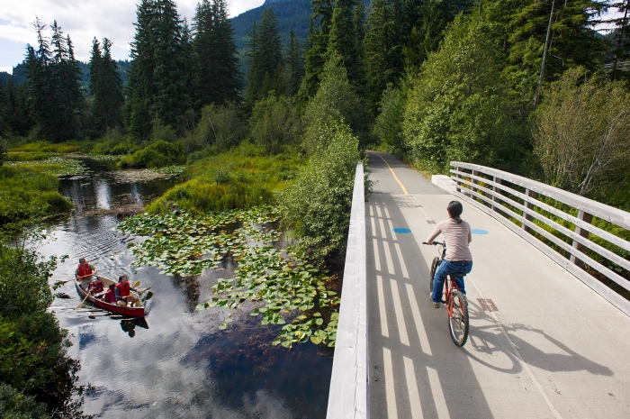 Two people in a canoe wave to a cyclist, pedaling across a bridge.