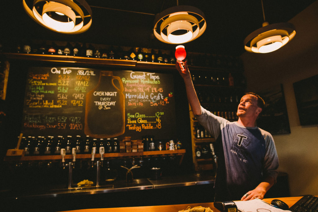 A man holds a pint on craft beer up to the light, inspecting the colour.