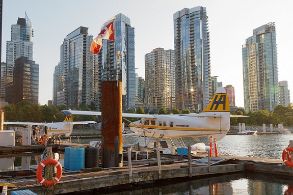 Two seaplanes are docked at a harbour as the Vancouver skyline rises in the background.