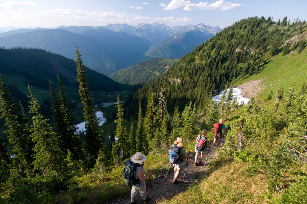 A group of hikers follow a path that overlooks a lush green valley.