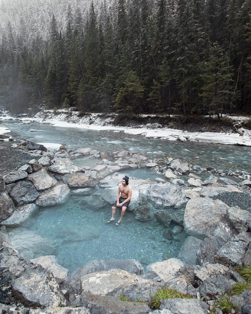 A young man dips his feet into Lussier Hot Springs, surrounded by a rocky terrain.