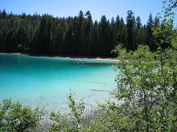 A couple canoes on a peaceful turquoise lake, surrounded by trees.