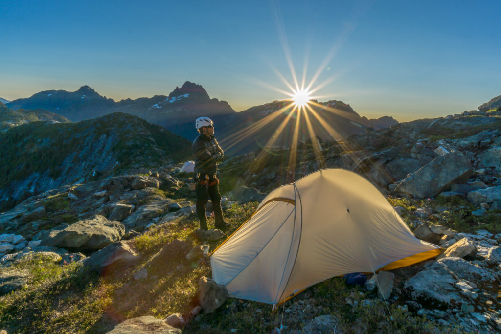A man wearing a white helmet stands next to a tent set up in a rocky landscape at sunset.