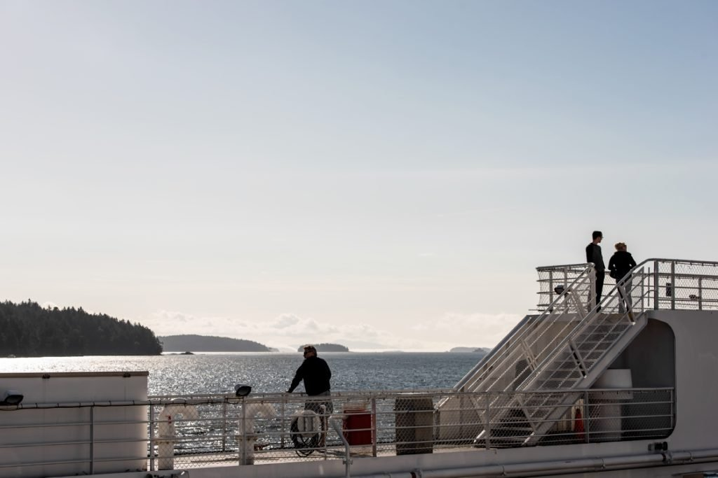 Passengers enjoy the view as a ferrie crosses the ocean.
