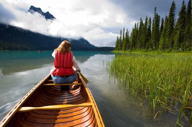 A woman paddles a canoe in calm waters, towards mist-covered mountains.