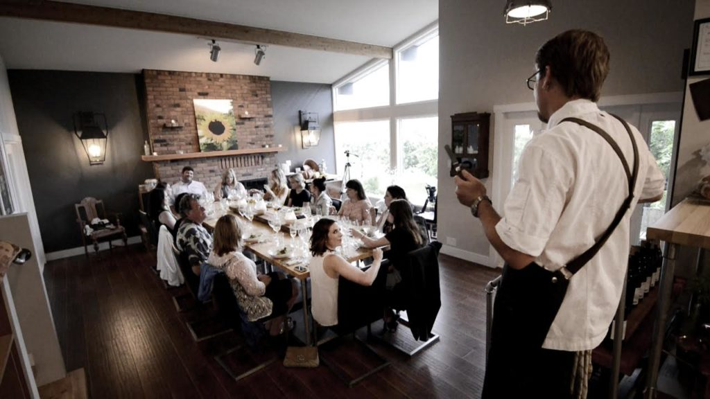 A chef speaks to diners seated in a modern dining room.