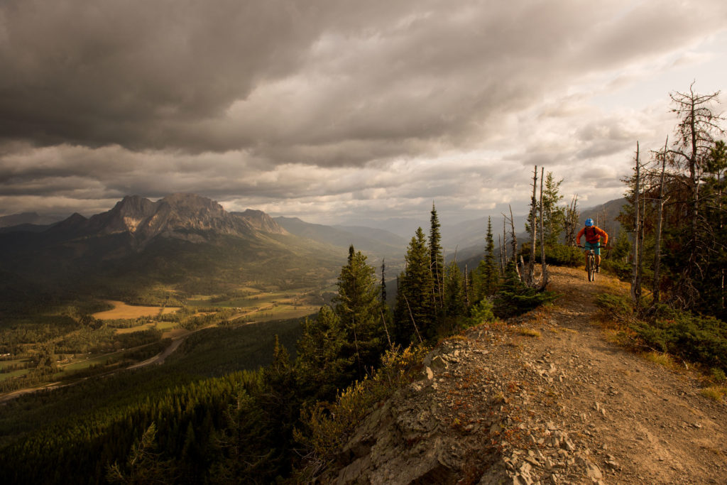 Mountain biking on a path that overlooks a deep valley under a cloudy sky.
