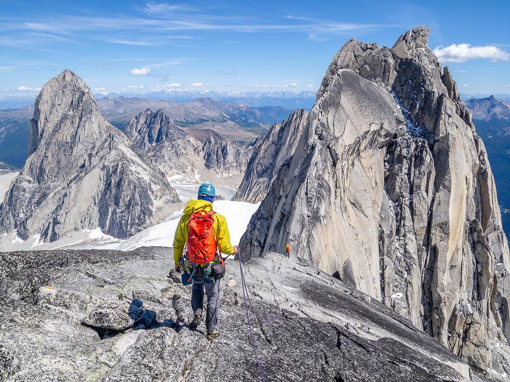 A hiker traverses a rocky, mountainous landscape.