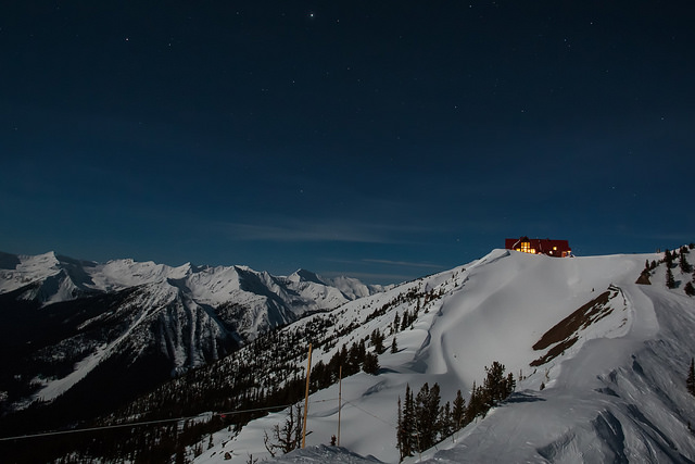 A brightly lit cabin sits at the top of a snow-covered mountain.