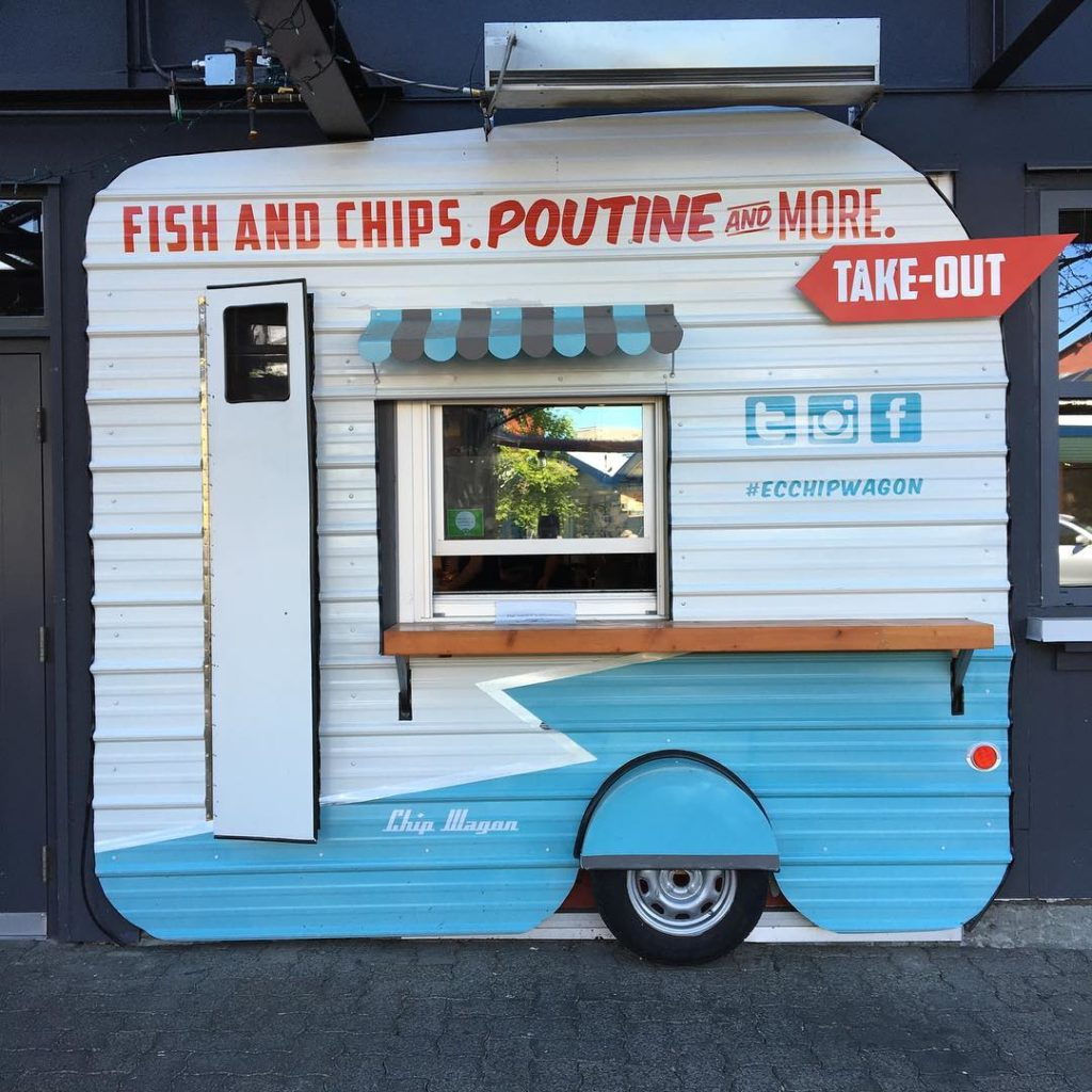 "A small white and blue food truck with the words ""Fish and Chips. Poutine and More!"" on the side."