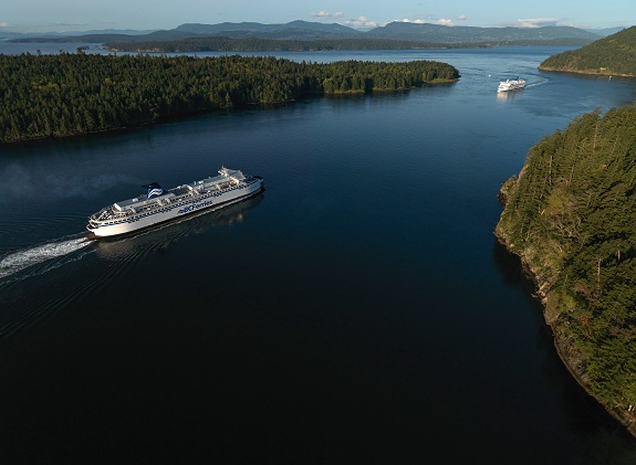 Two cruise ships sail through deep blue waters and green islands.