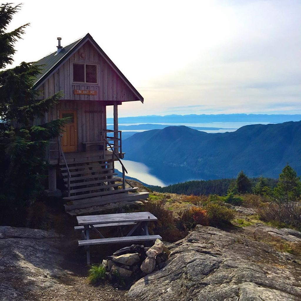 A log cabin sits on top of a mountain, overlooking the ocean.