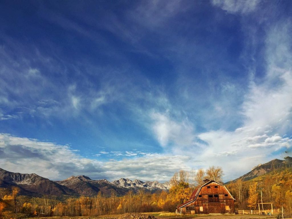 A rustic log cabin surrounded by fall colours and snow-capped mountains.