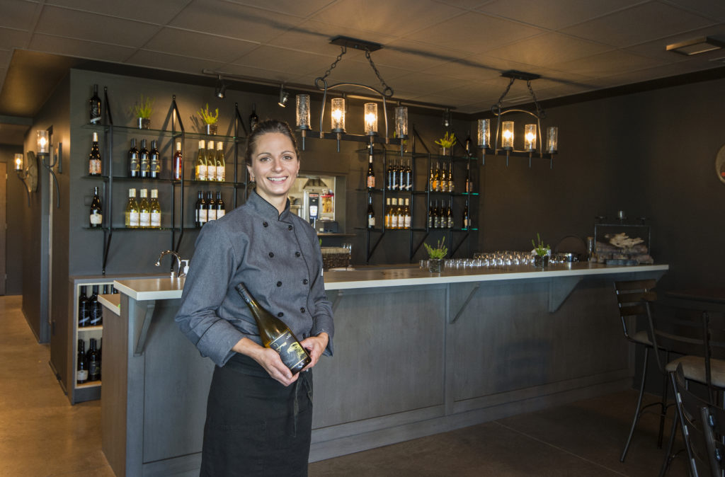 A smiling woman stands in front of a modern bar, holding a bottle of wine.