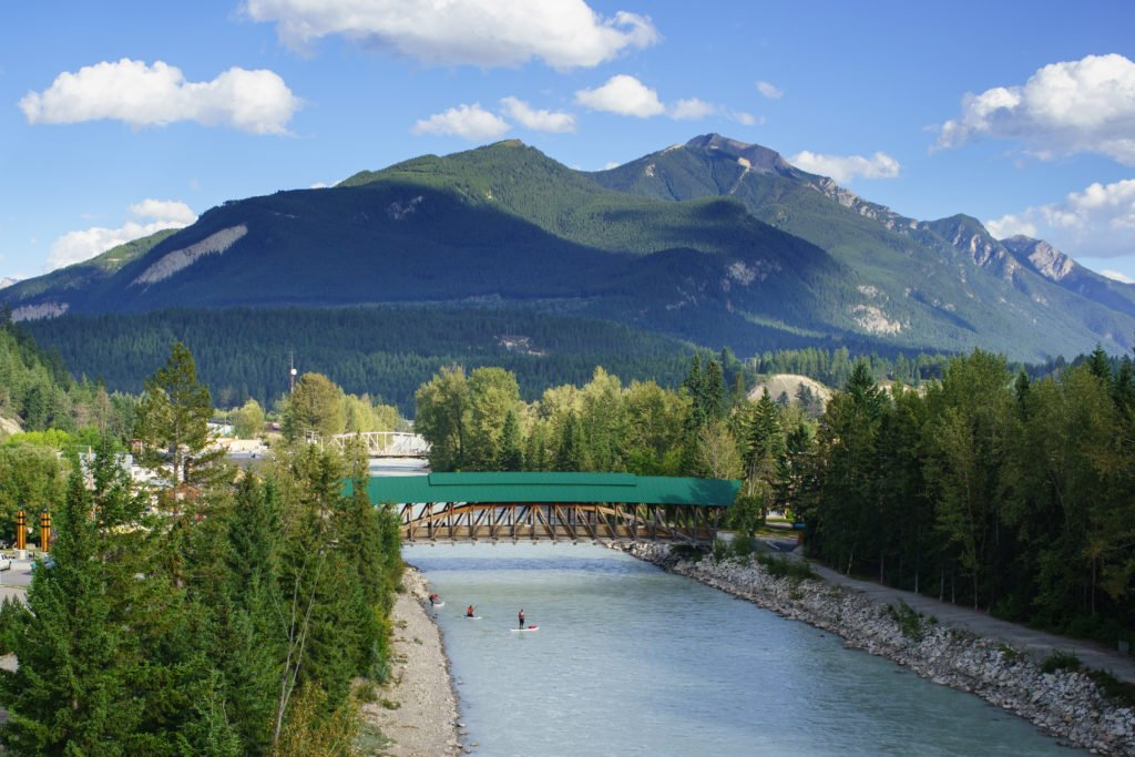 A lush mountain range looks over a small body of water and a green pedestrian bridge.