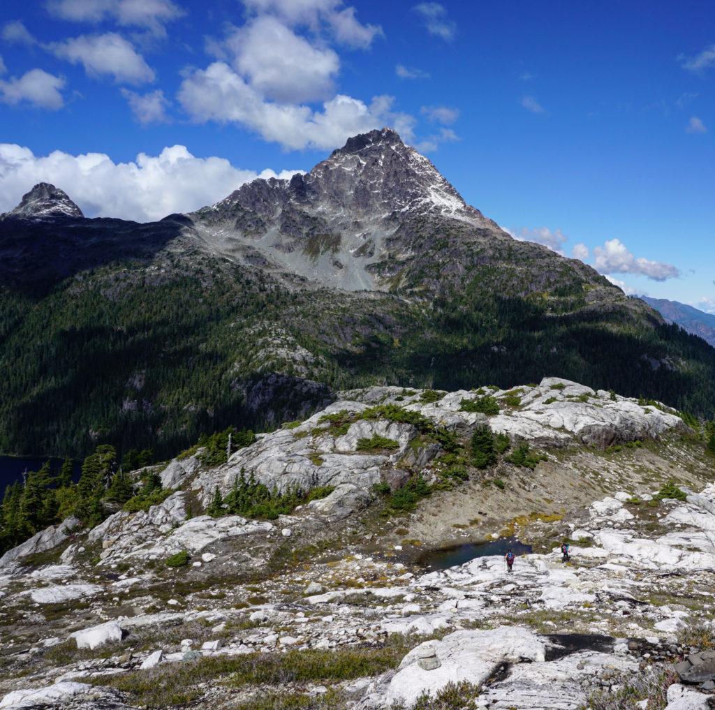 A rocky landscape and mountain peak under a blue sky.