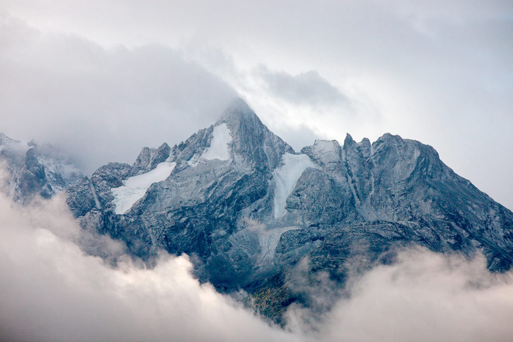 A spectacular mountain peak showing through a break in the clouds.
