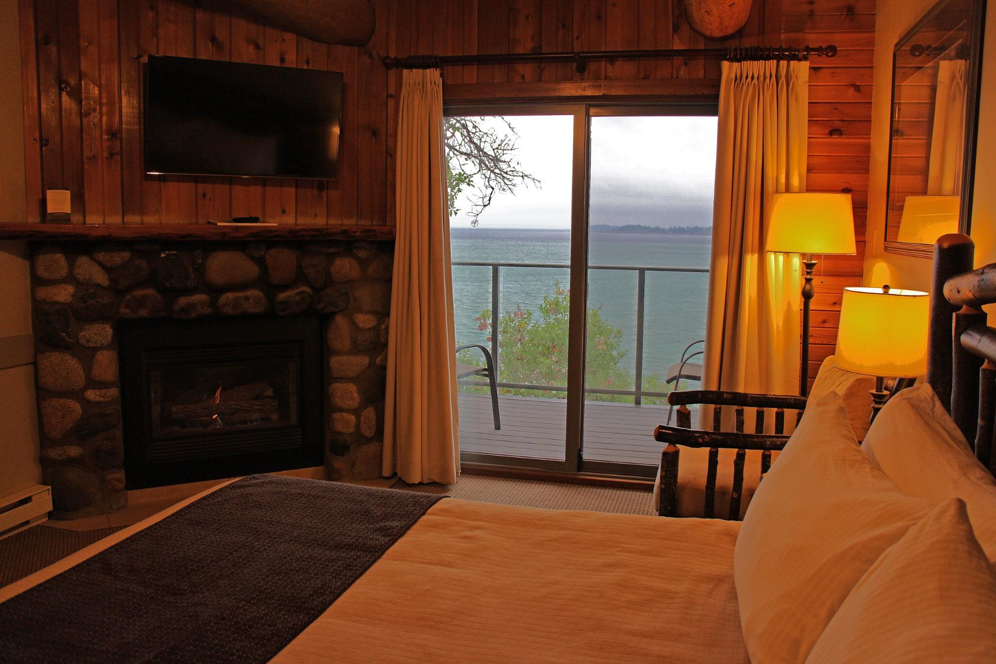 The cozy interior of a resort bedroom with a fireplace and private balcony overlooking the water.