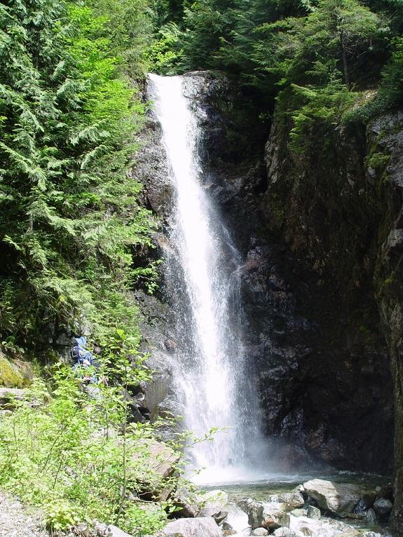 A rocky terrain surrounds a stunning waterfall.