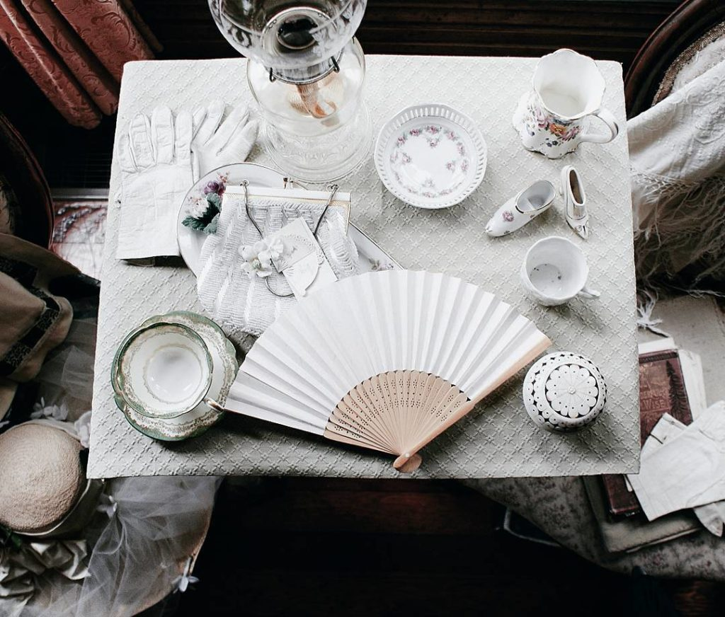 A beautiful table setting of china tea cups, saucers, white gloves, and a fan.