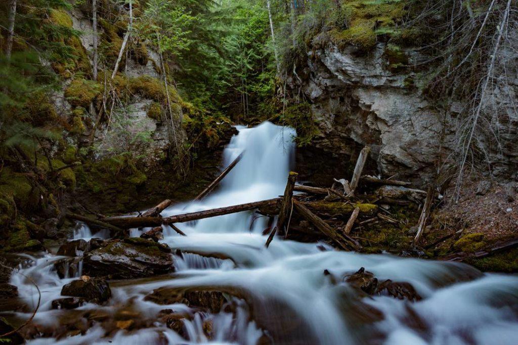 A misty stream flows through a rugged terrain.