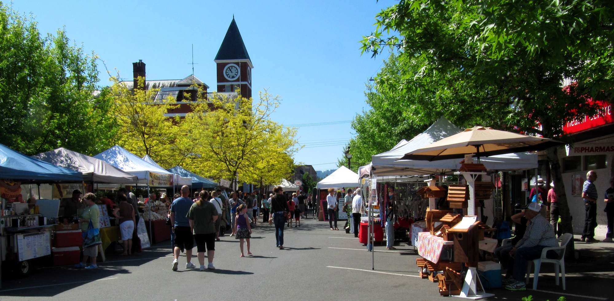 An outdoor market is set up on a sunny city street.