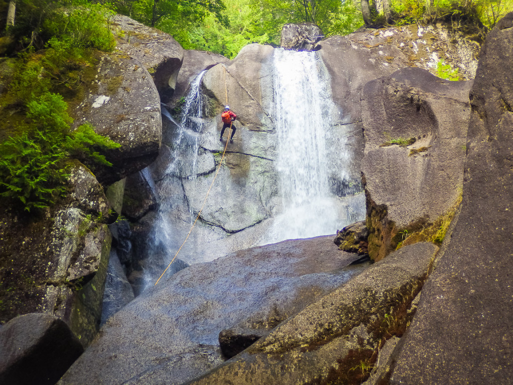 A woman rappels down the side of a waterfall.
